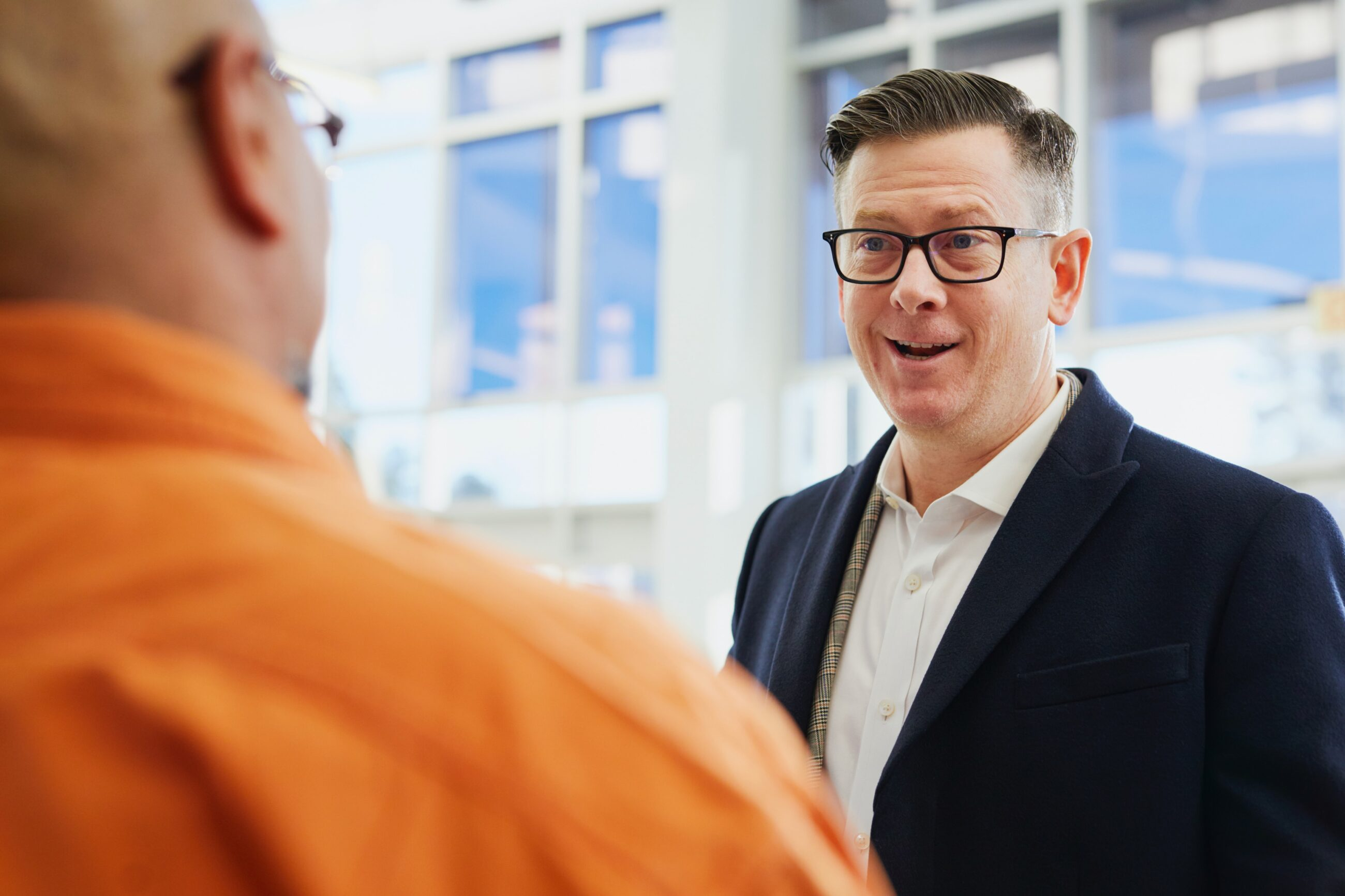 man in black suit and white shirt speaks to a man in an orange shirt with his back to the camera