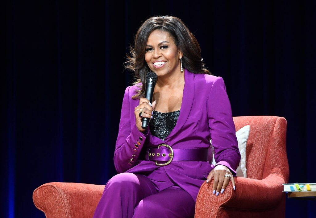 Michelle Obama holding a microphone and sitting on a red chair being interviewed
